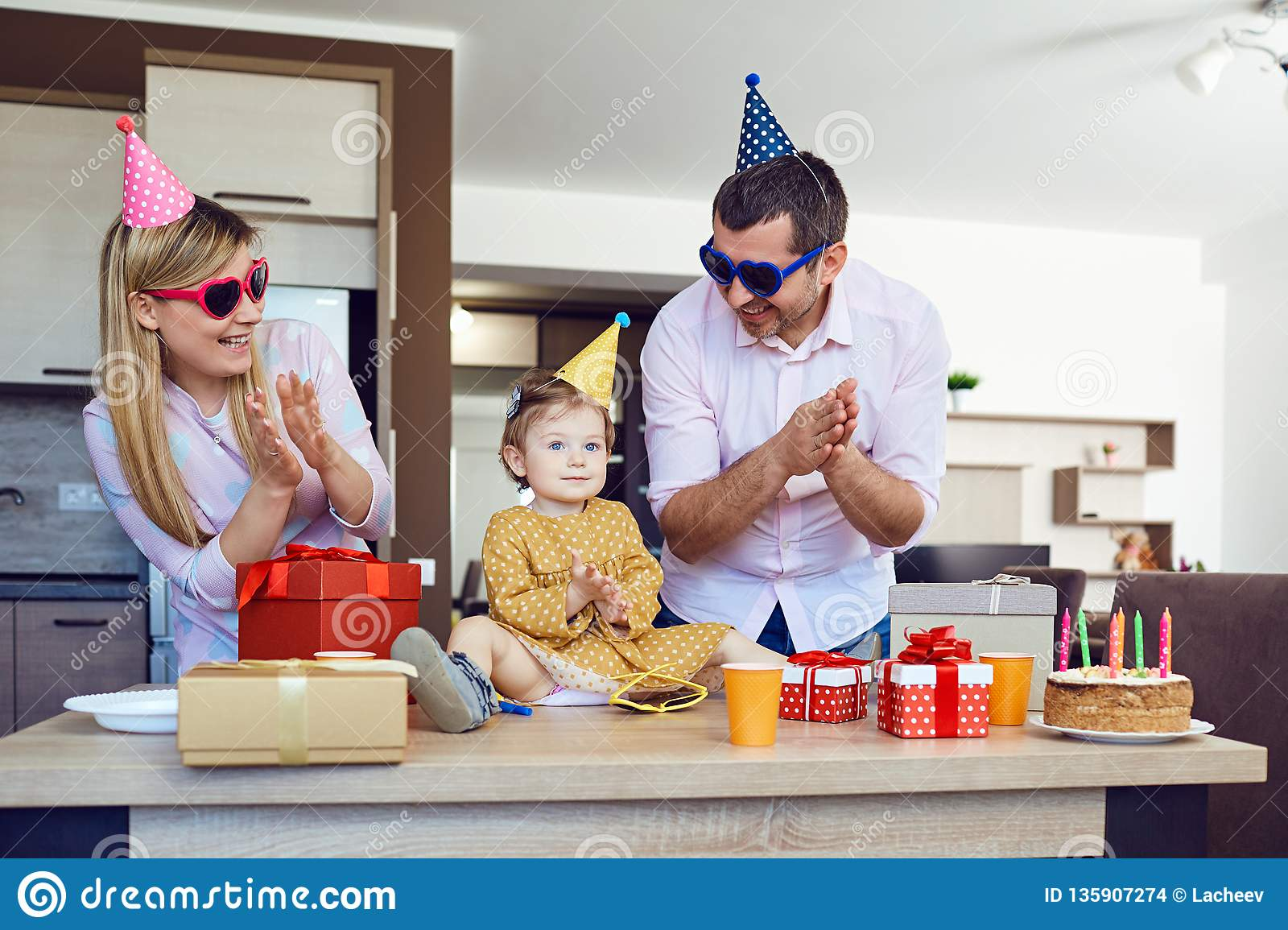 A family with a cake congratulates a happy child on his birthday