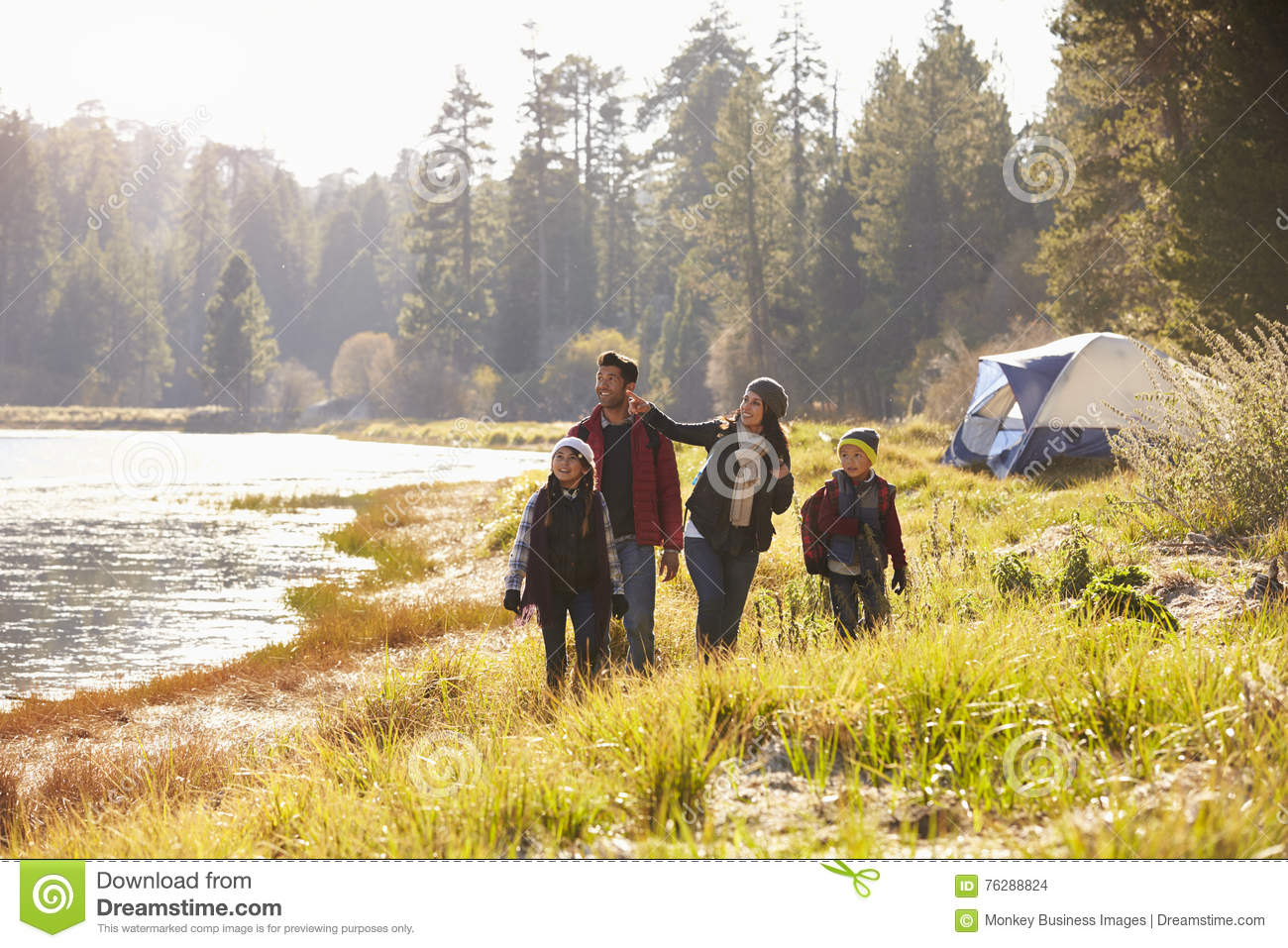 Family on a camping trip walking near a lake looking away