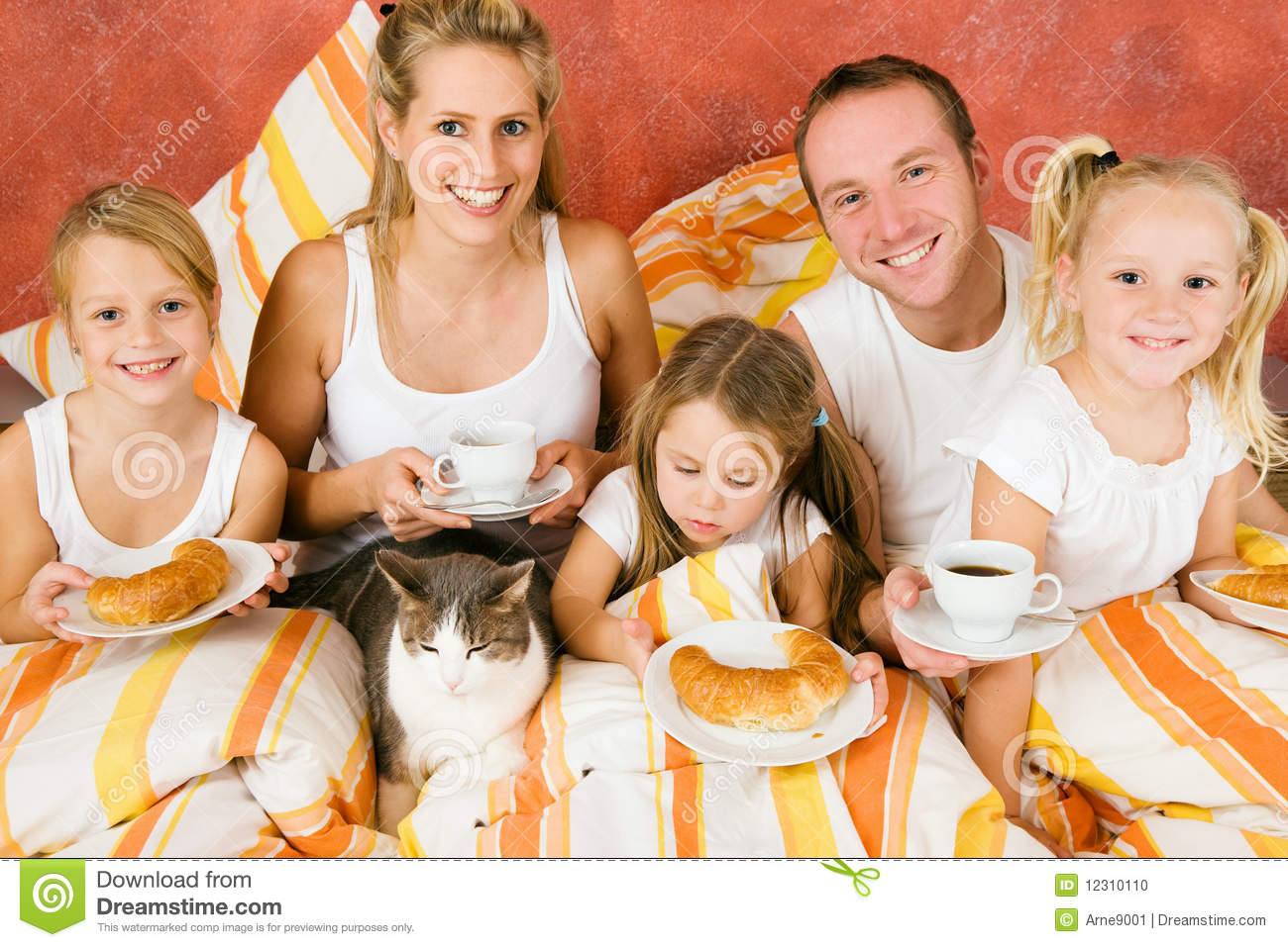 Family and cat having breakfast in bed