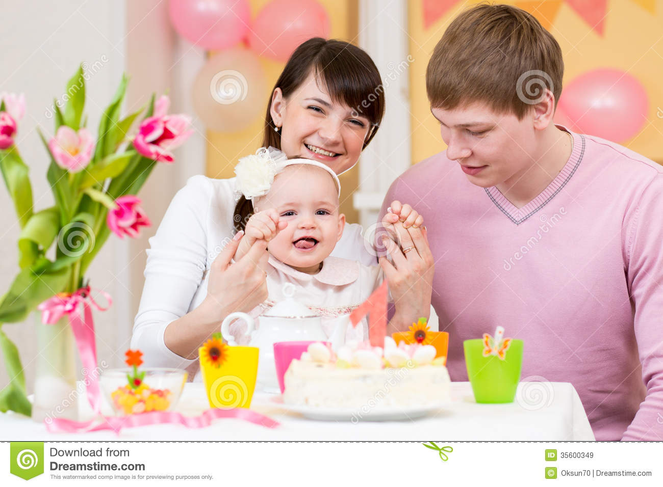Family celebrating first birthday of baby girl