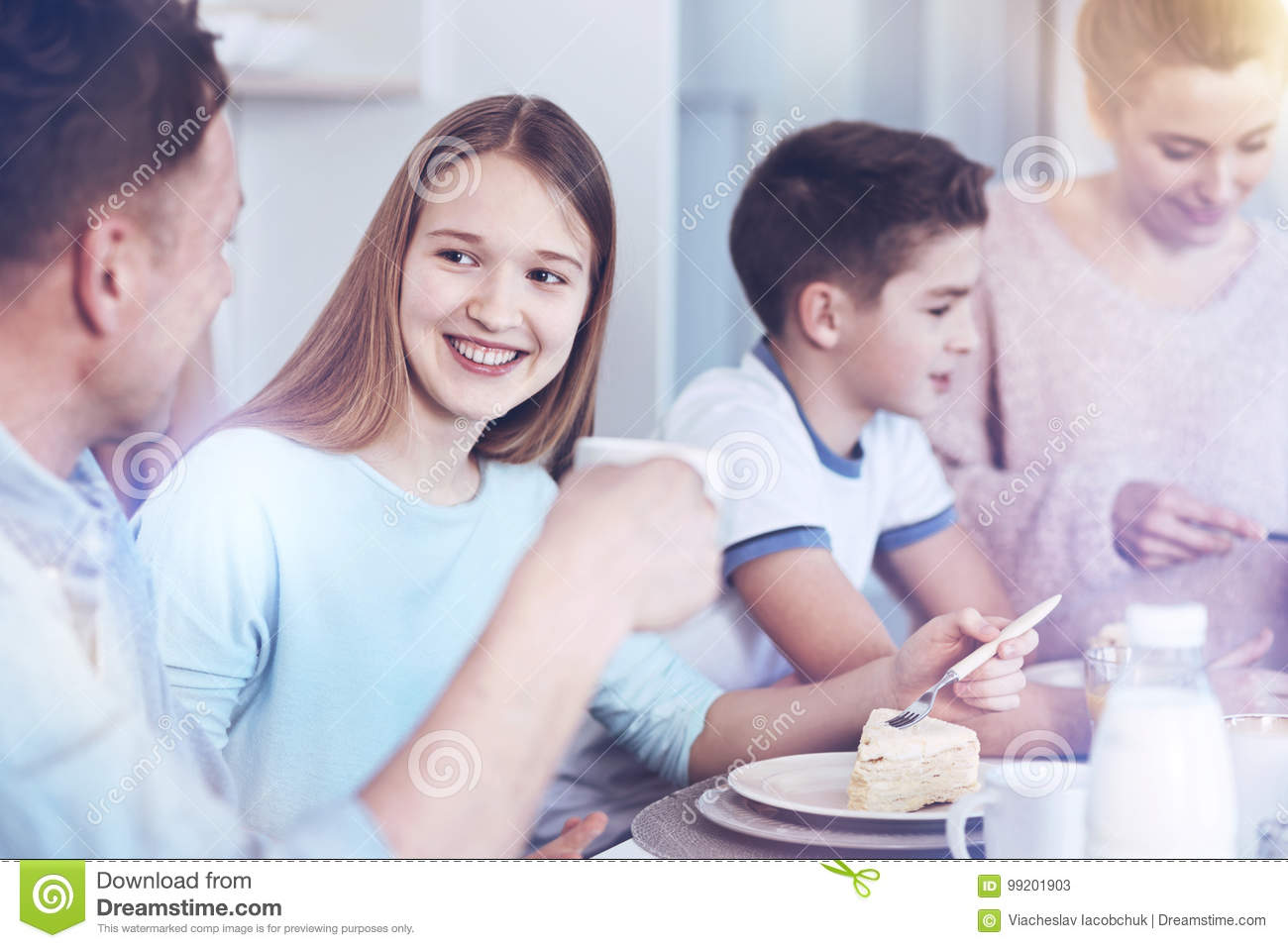 Cheerful Girl Talking To Father While Eating Piece Of Cake