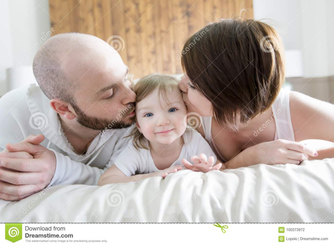 A family with child happy parents playing with baby on bed