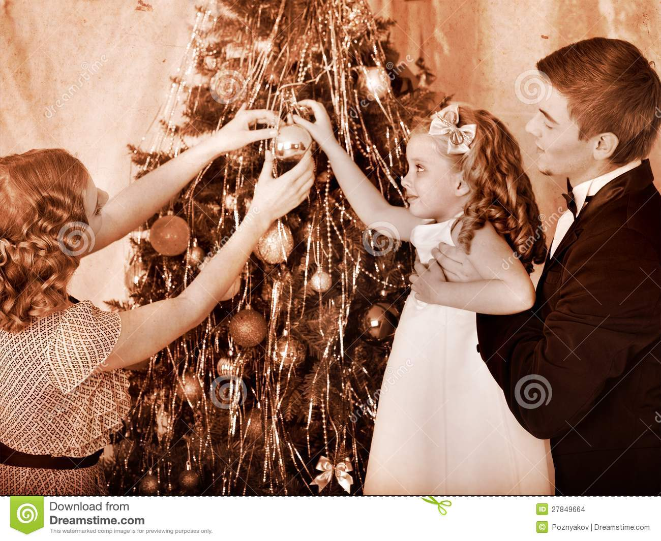 Family With Children Dressing Christmas Tree. Stock Photo