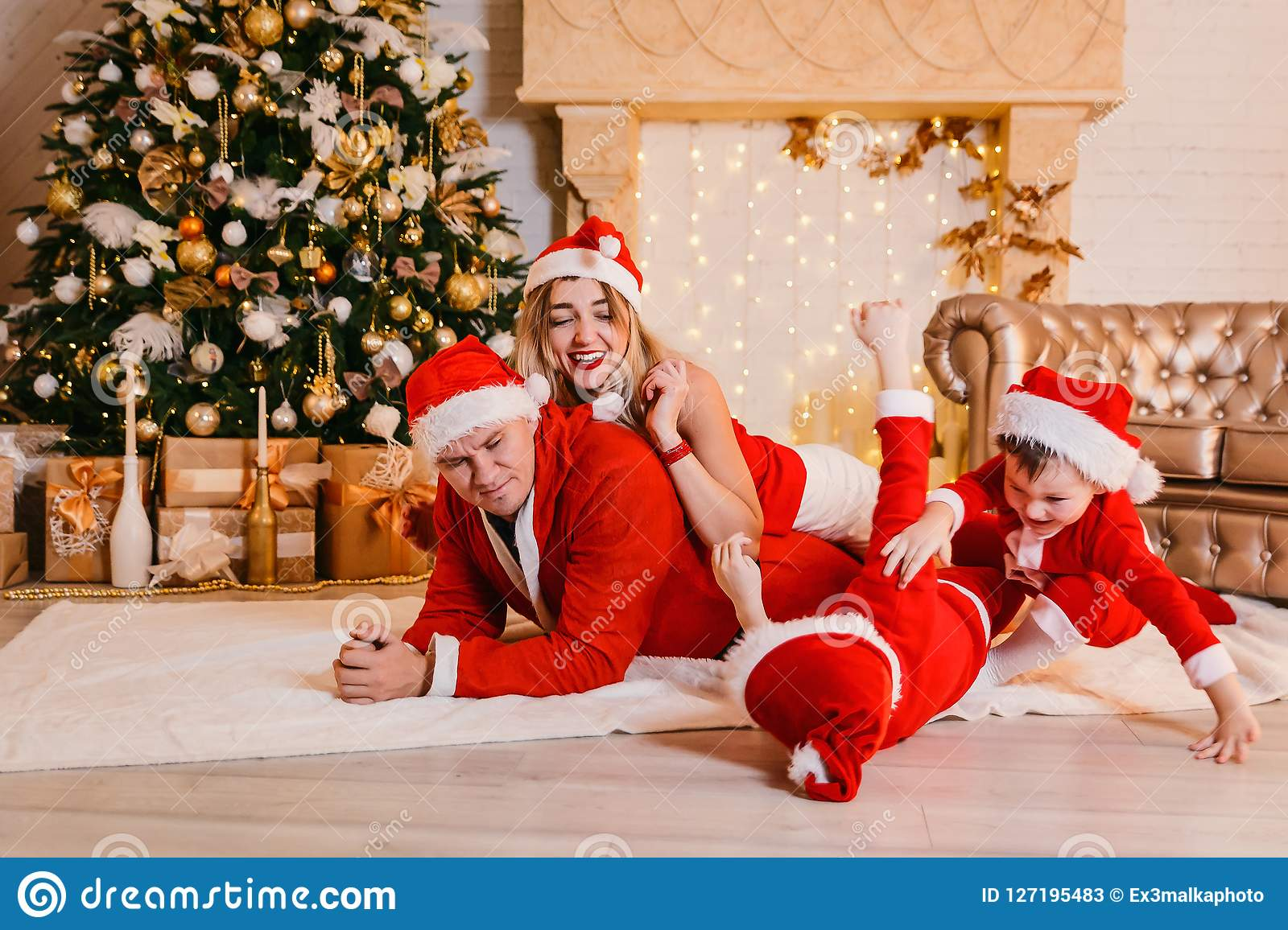 Family with children having fun under the Christmas tree