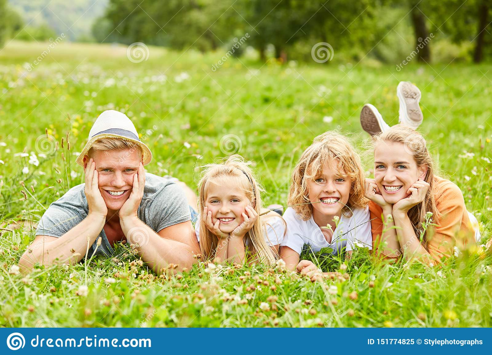 Family and children lie on a meadow