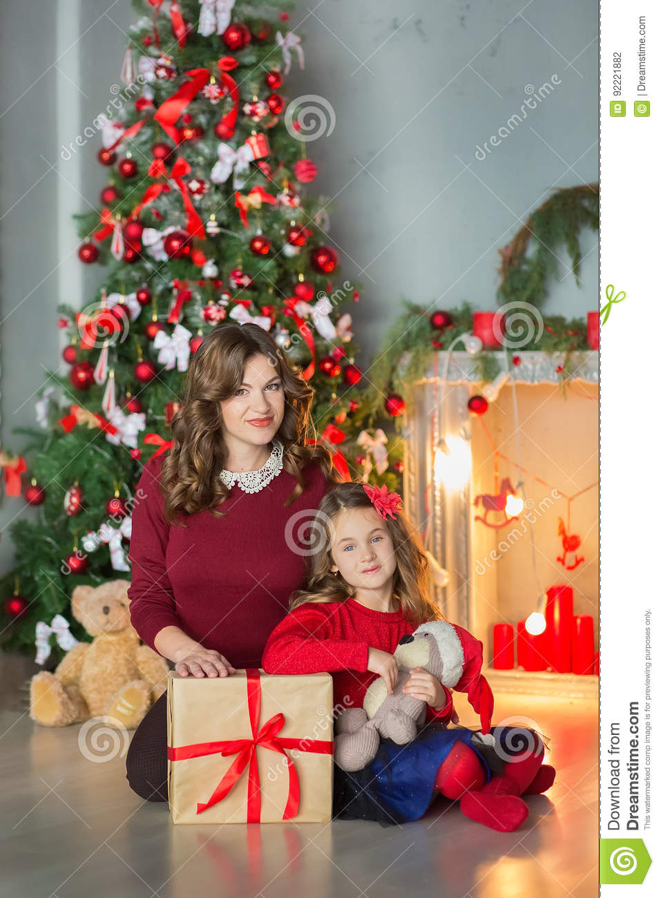 Family on Christmas eve at fireplace. Kids opening Xmas presents. Children under Christmas tree with gift boxes. Decorated living