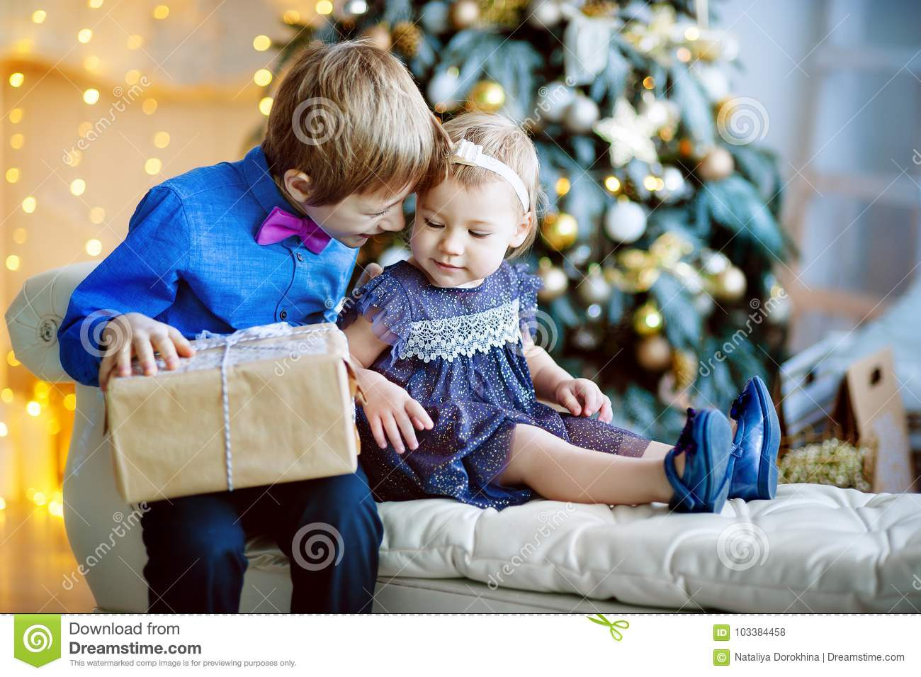 Family on Christmas eve at fireplace. Kids opening Xmas presents. Children under Christmas tree with gift boxes