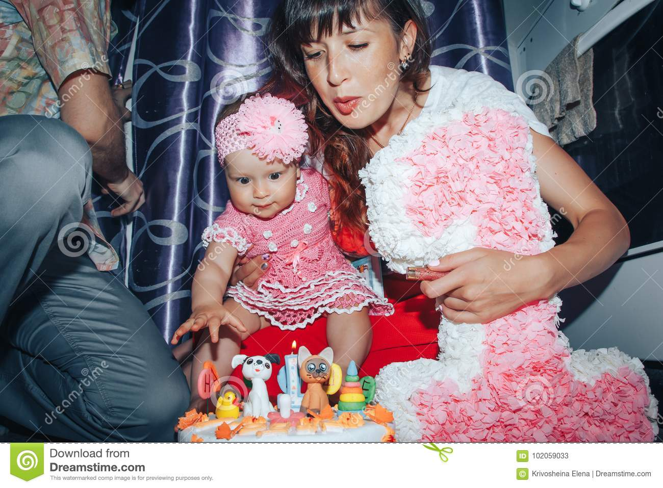 Family consisting father, mother and daughter celebrate birthday of one-year-old girl