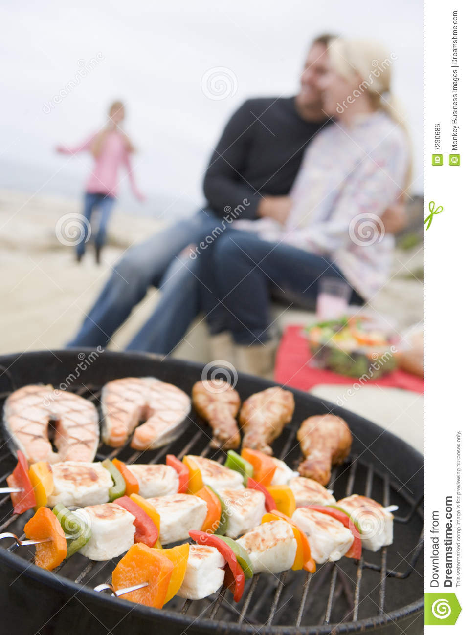 Family Cooking Barbeque On A Beach