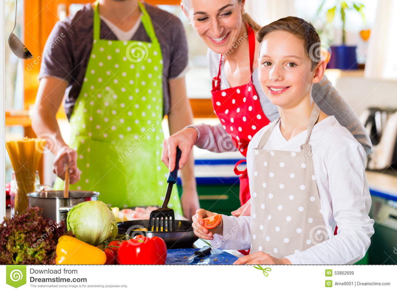 Family Cooking Healthy Food In Domestic Kitchen Stock Image