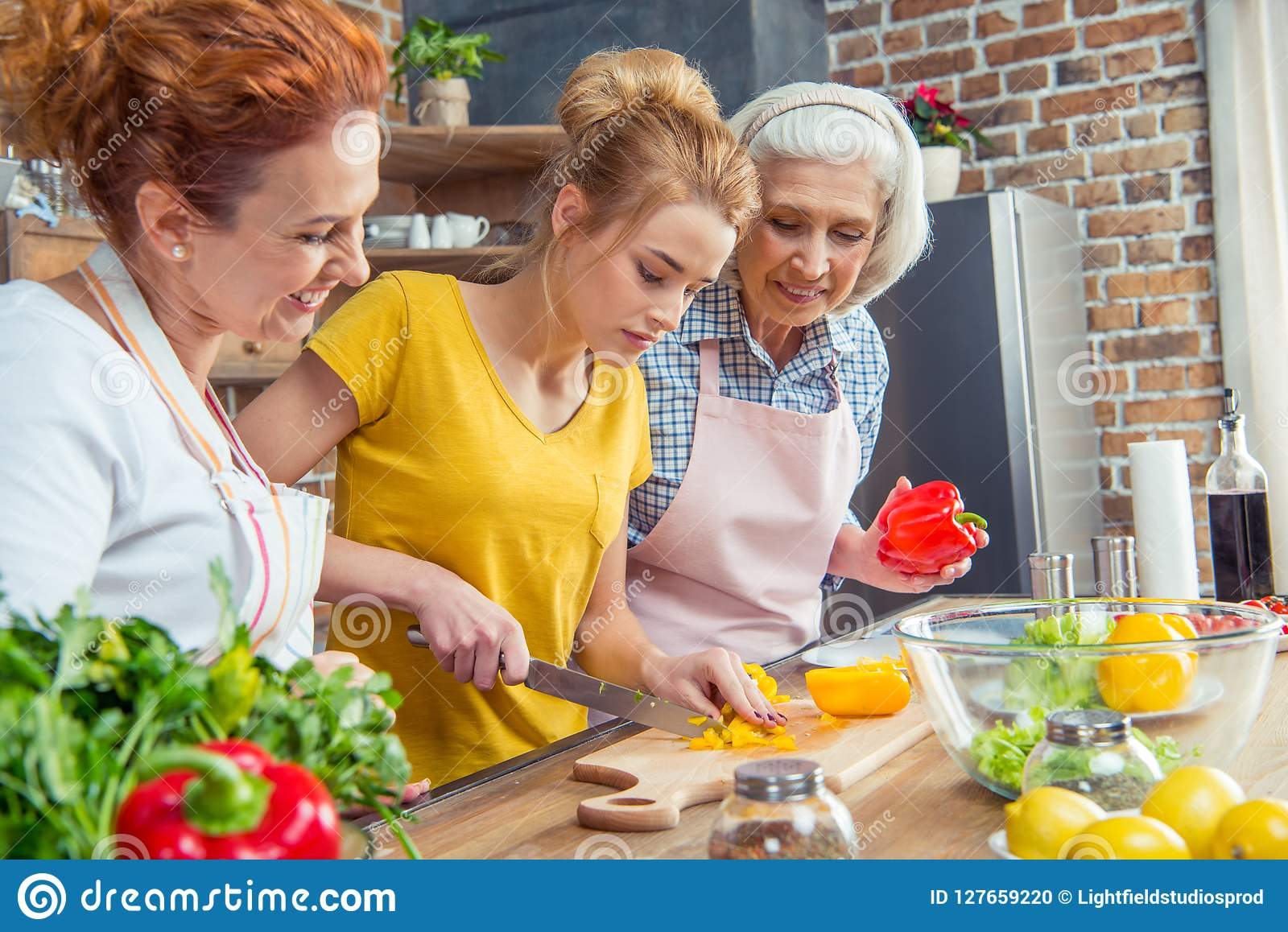 Happy three-generation family cooking together vegetable salad