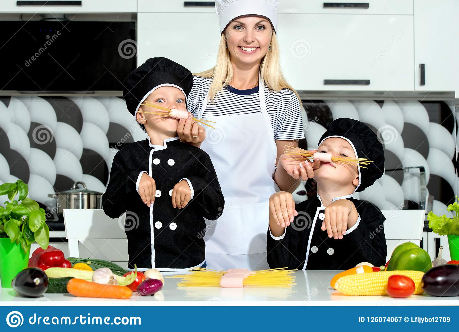 A family of cooks.Mother and children prepares spaghetti in kitchen.