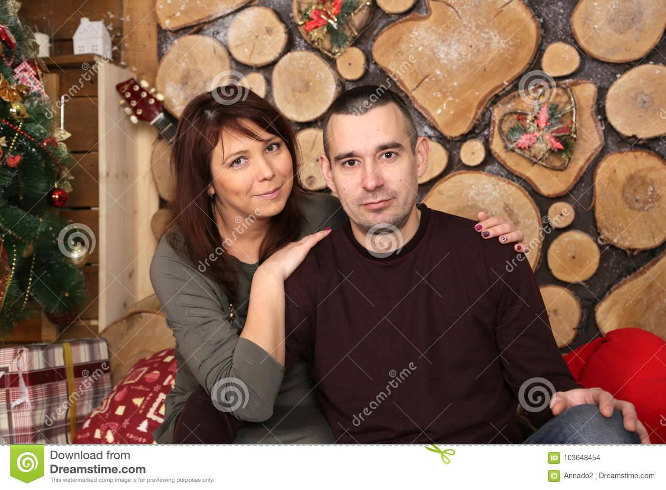 young married couple at christmas tree with gifts portrait in a beautiful festive interior