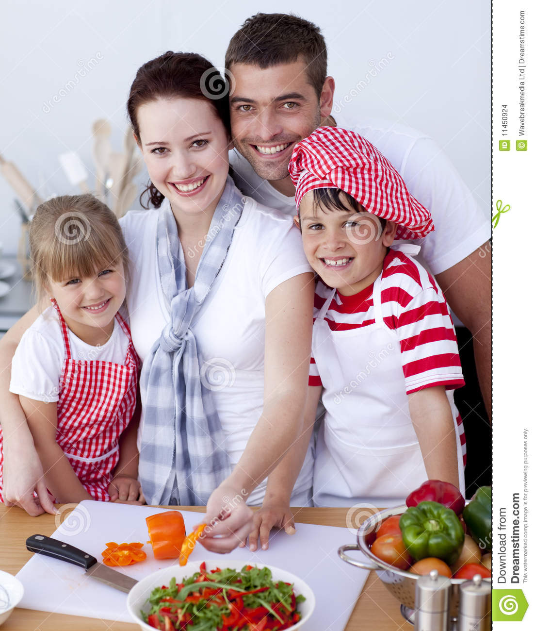 Family cutting colourful vegetables in kitchen