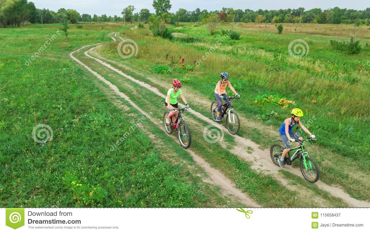 Family cycling on bikes outdoors aerial view from above, happy active mother with children have fun, family sport