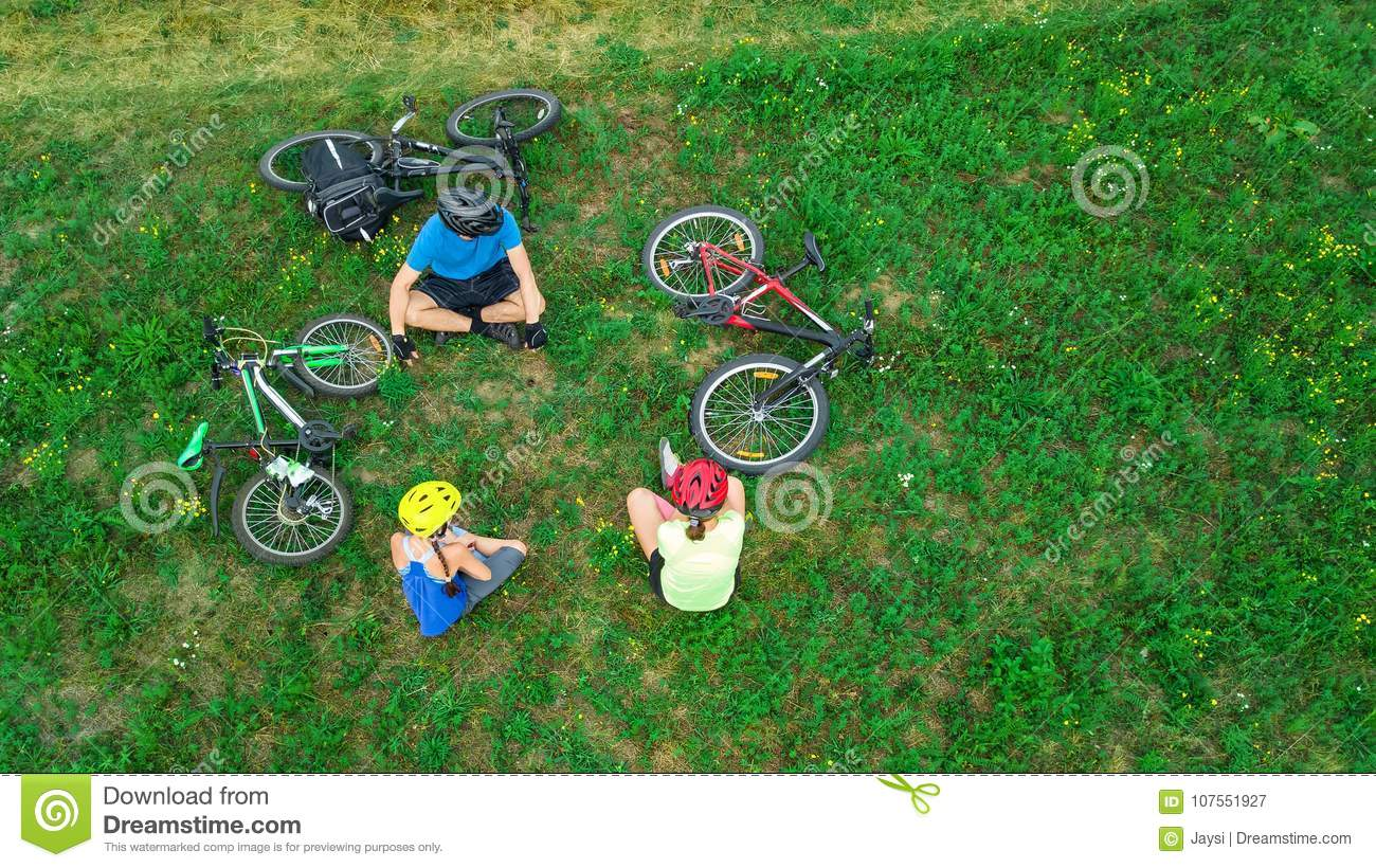 Family cycling on bikes outdoors aerial view from above, happy active parents with child have fun and relax on grass, family sport