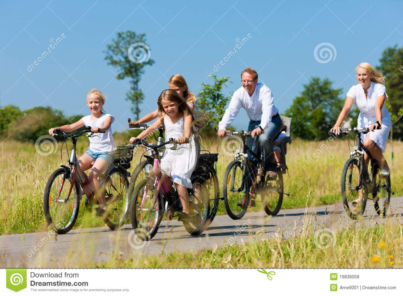 Family Cycling Outdoors In Summer Stock Photo