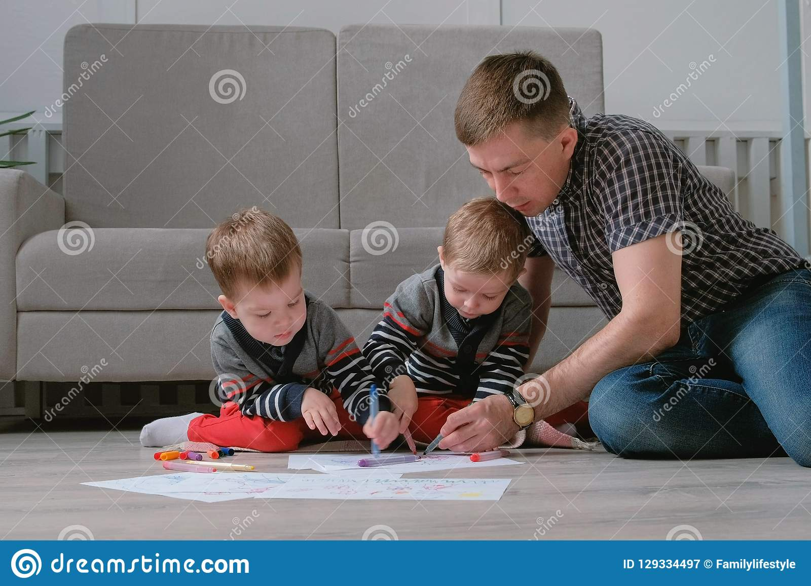 Family dad and two twin brothers draw together markers and felt pens sitting on the floor.