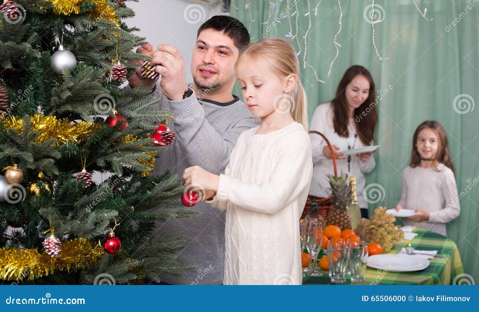 Family Decorating Christmas Tree At Home Stock Photo