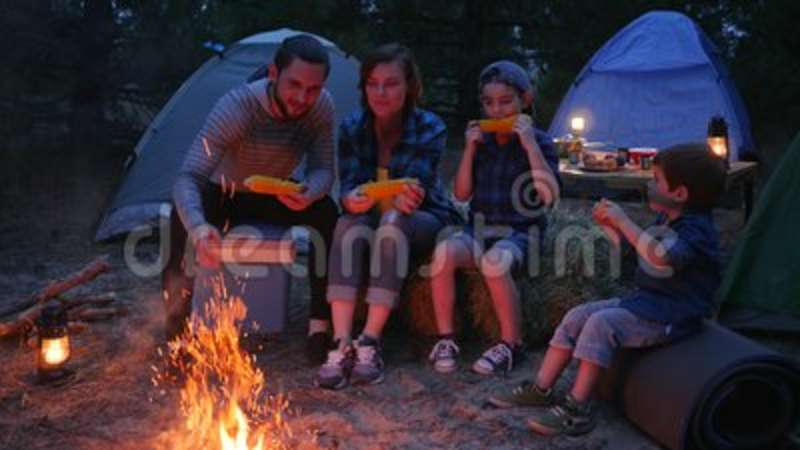 Family dinner near flames on nature, family eat corn with salt, travel camping, mama, daddy and sons eat up fresh yellow
