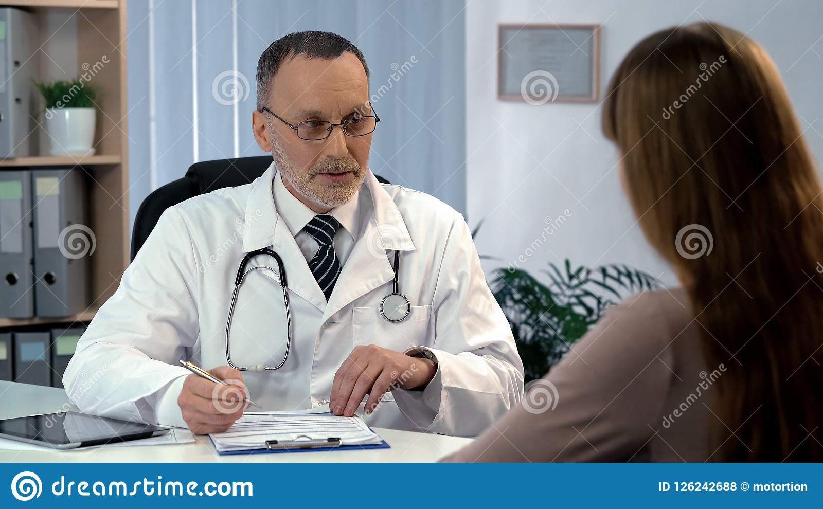 Family doctor listening to patient, filling out medical insurance, health care