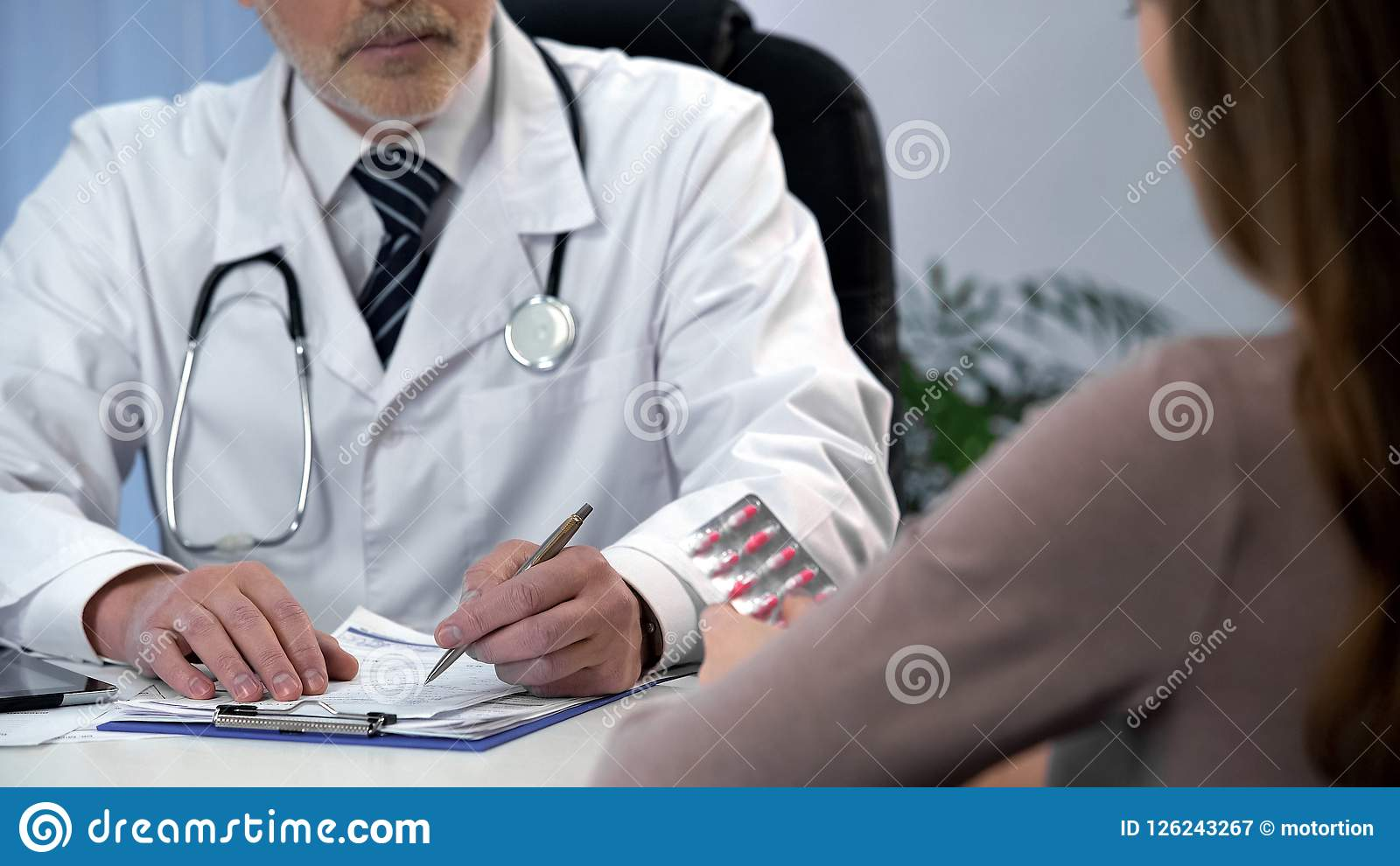 Family doctor prescribing treatment and giving pills to patient, health care