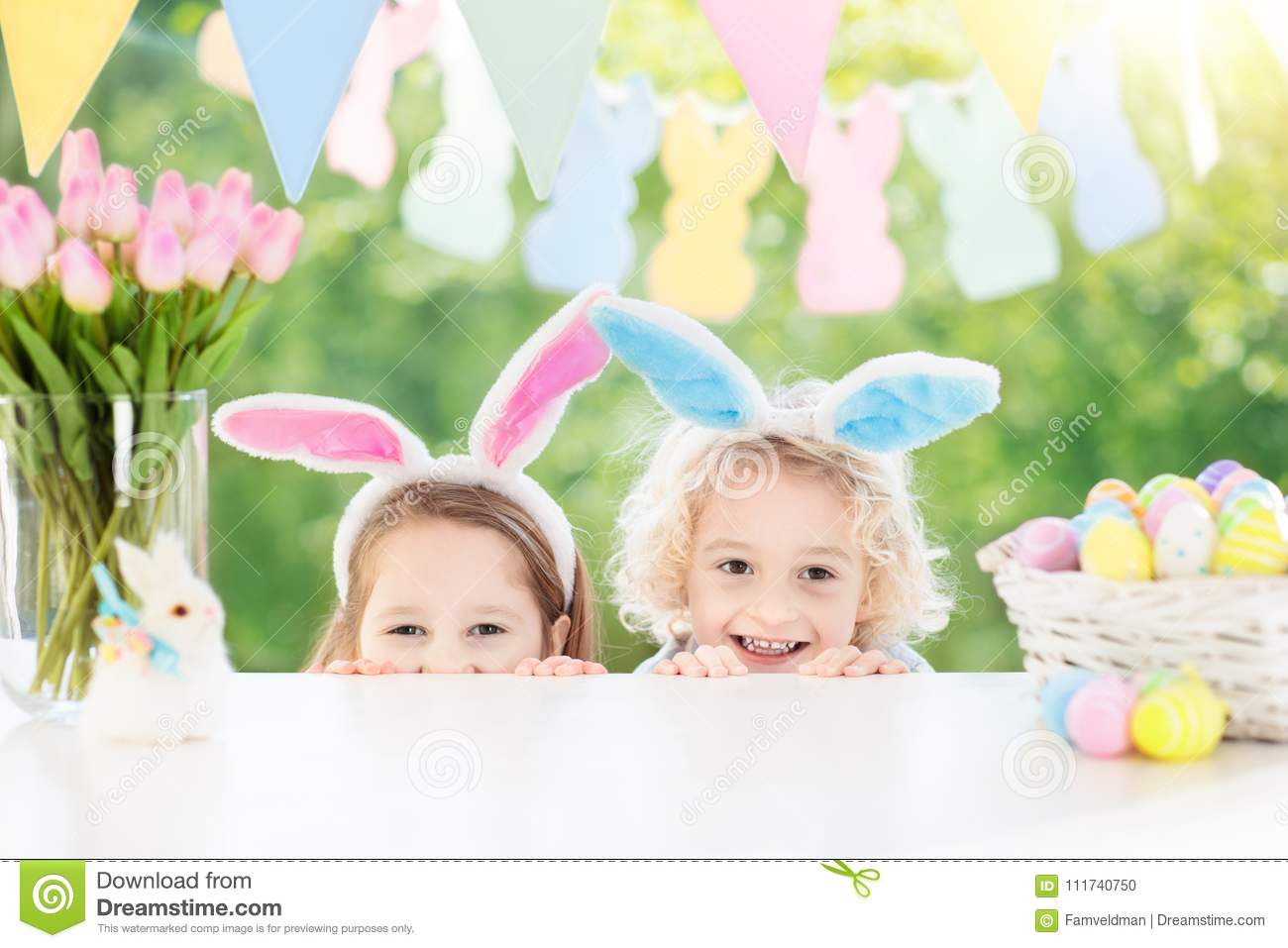 Kids with bunny ears and eggs on Easter egg hunt.