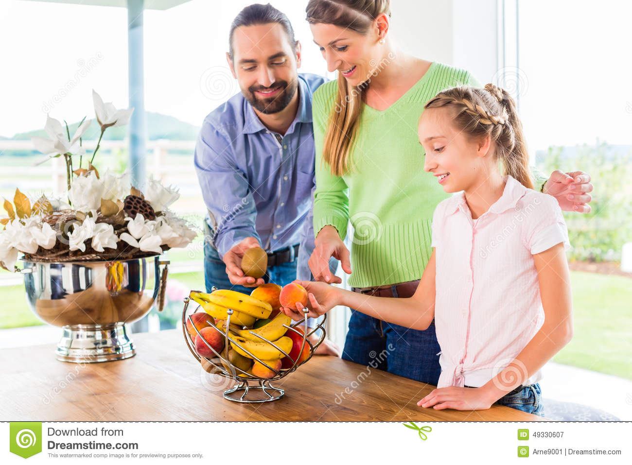 Family eating fresh fruits for healthy living in kitchen