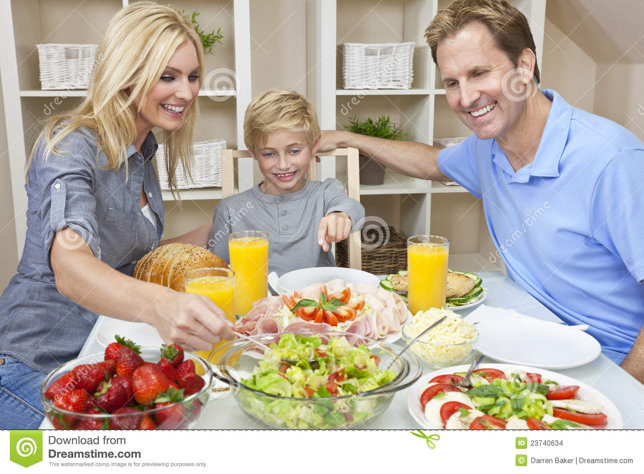 Family eating healthy food salad at dining table stock for Eating table