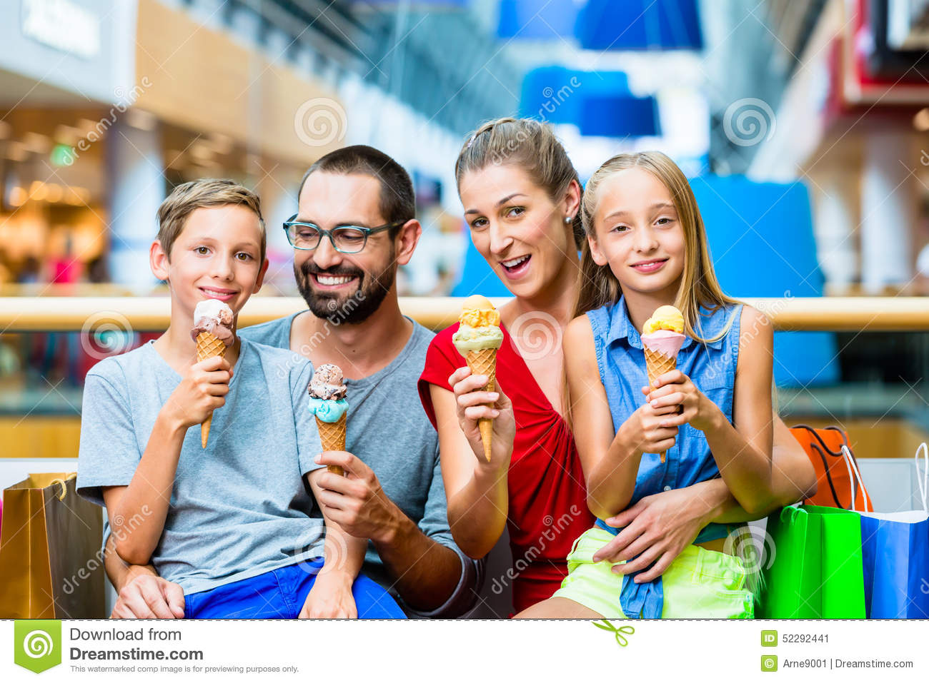 Family Eating Ice Cream In Mall With Bags Stock Image ...