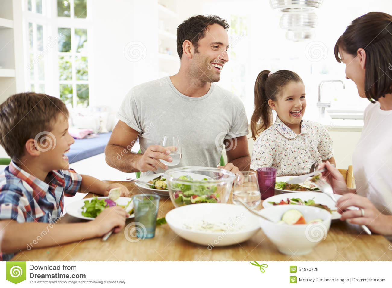 Family eating meal around kitchen table together stock for Eating table
