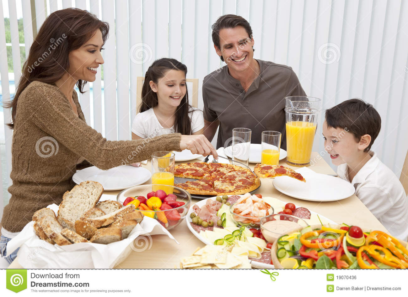 Family eating pizza salad at dining table royalty free for Eating table