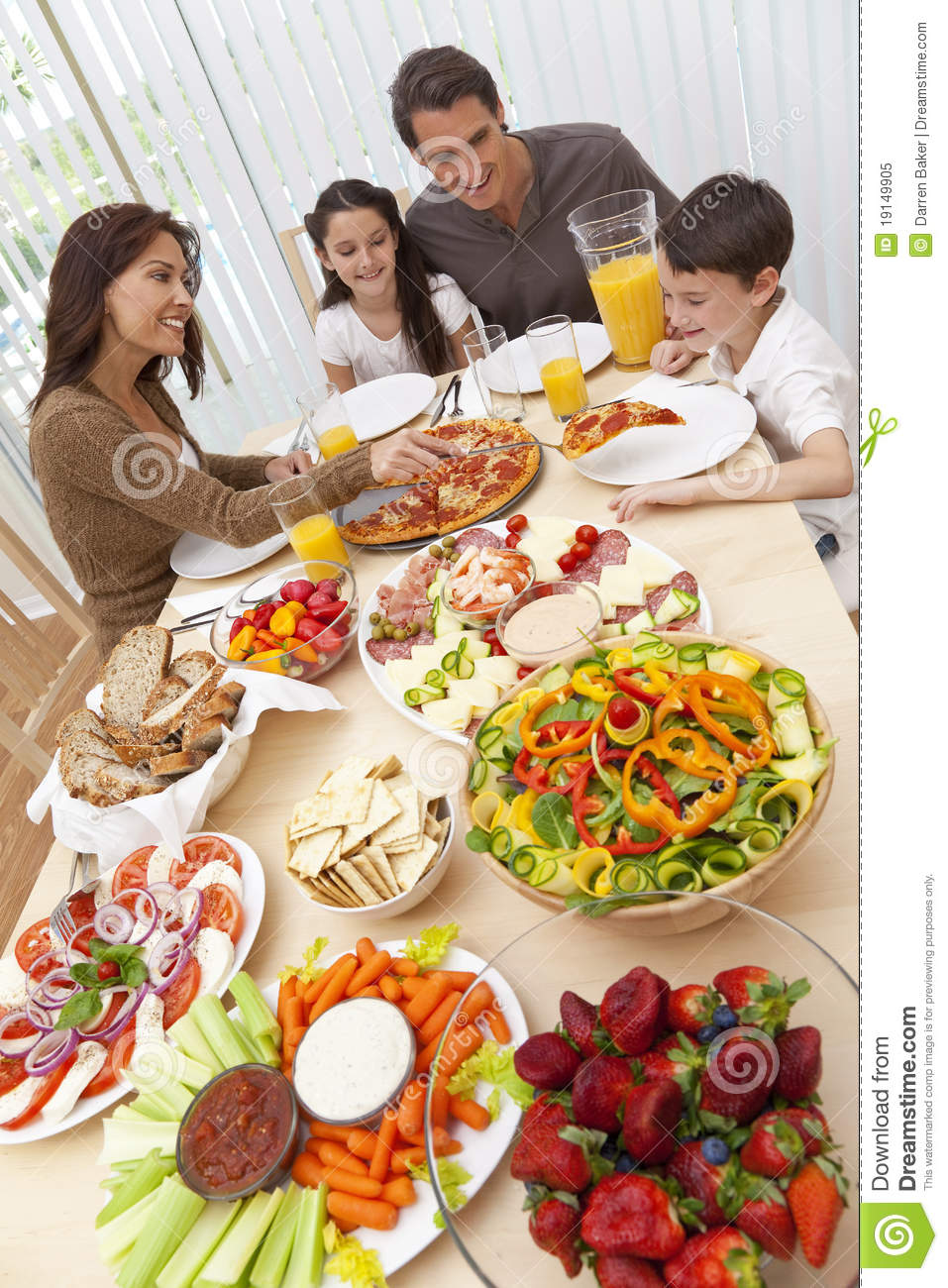 Family Eating Pizza & Salad At Dining Table