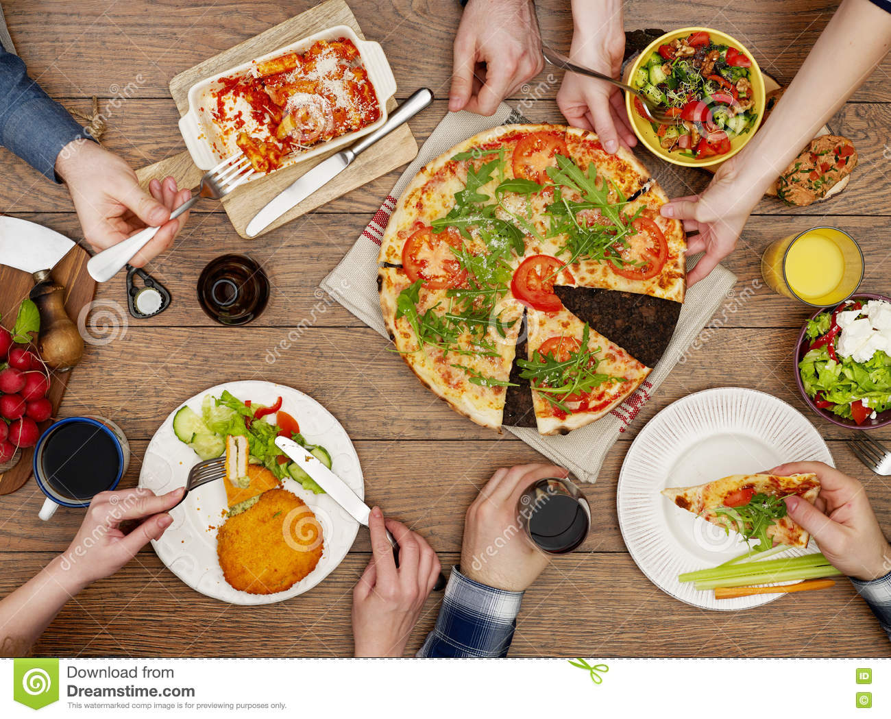 Family eating pizza salad at dining table stock photo for Eating table