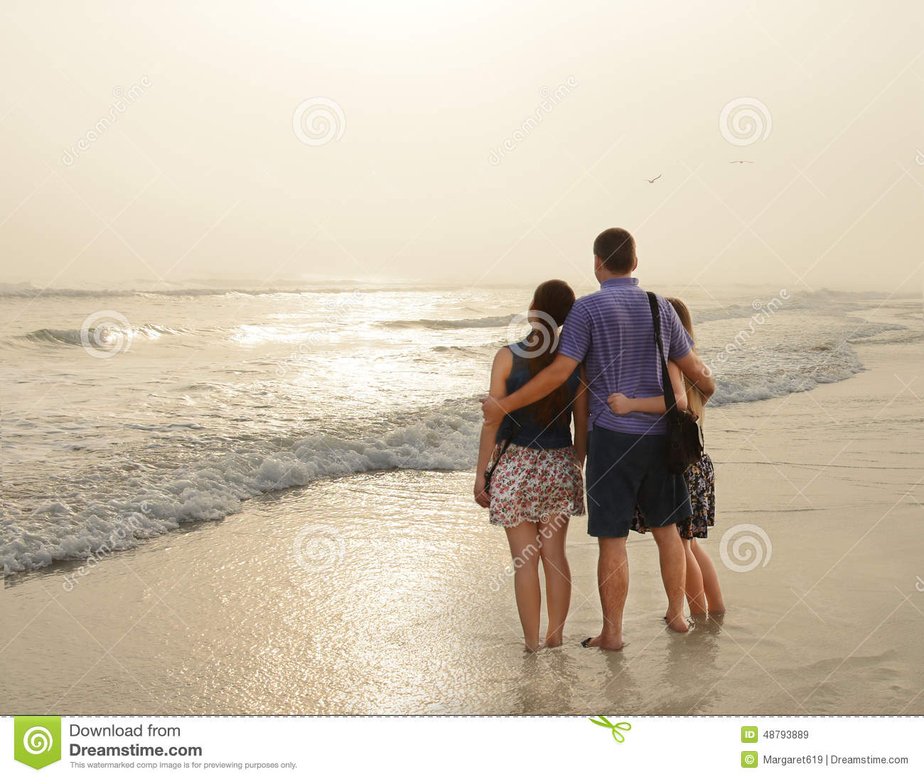 Family Enjoying Time Together On Beautiful Foggy Beach