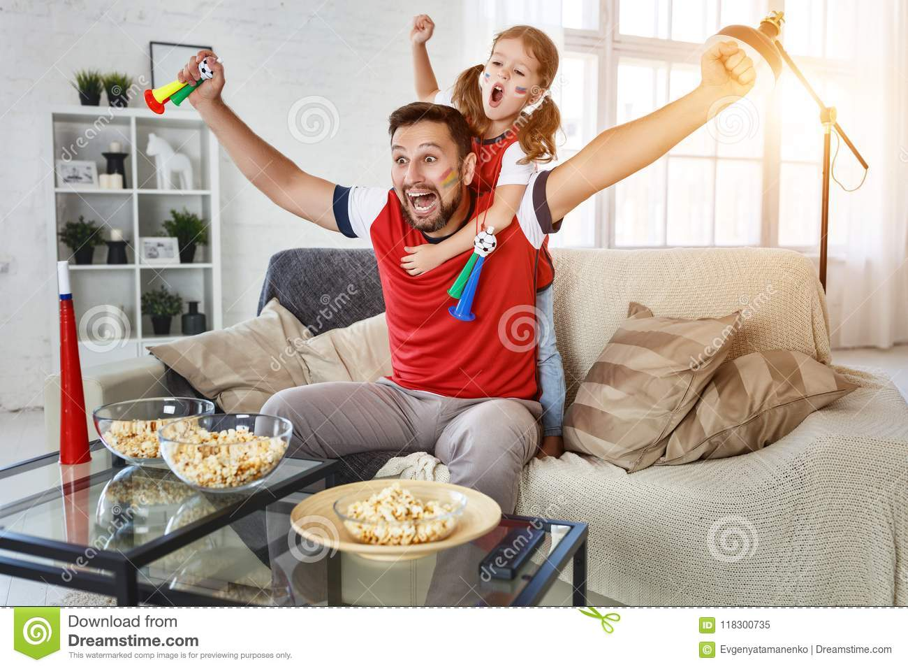 Family of fans watching a football match on TV at home