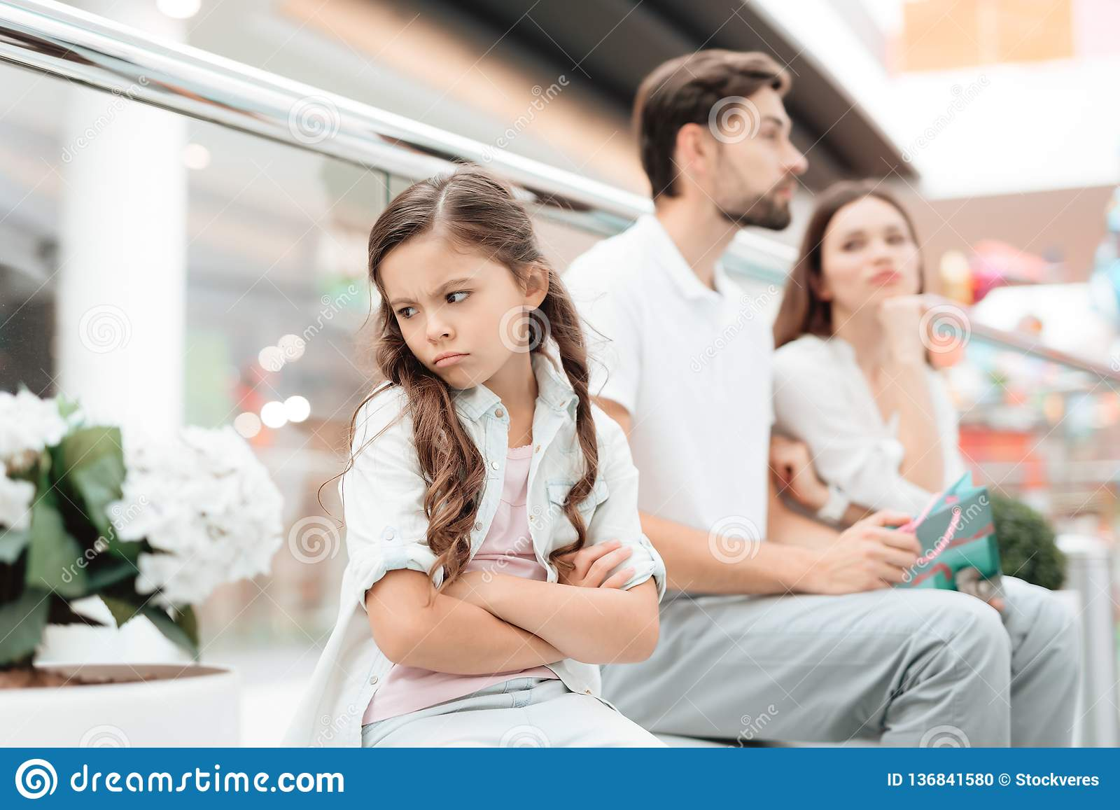 Family, father, mother and daughter are sitting on bench in shopping mall. Girl is angry and sad.