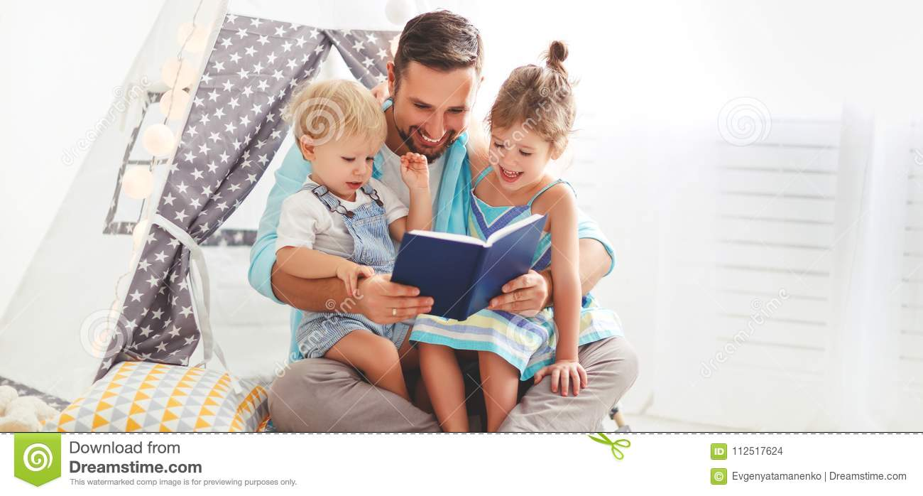 Family father reading to children book in tent at home