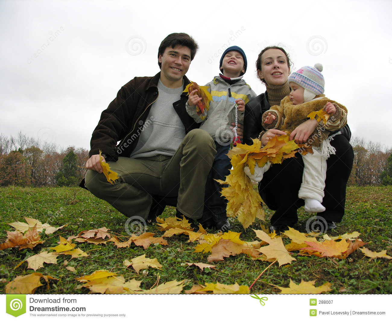 Family of four with autumn leaves
