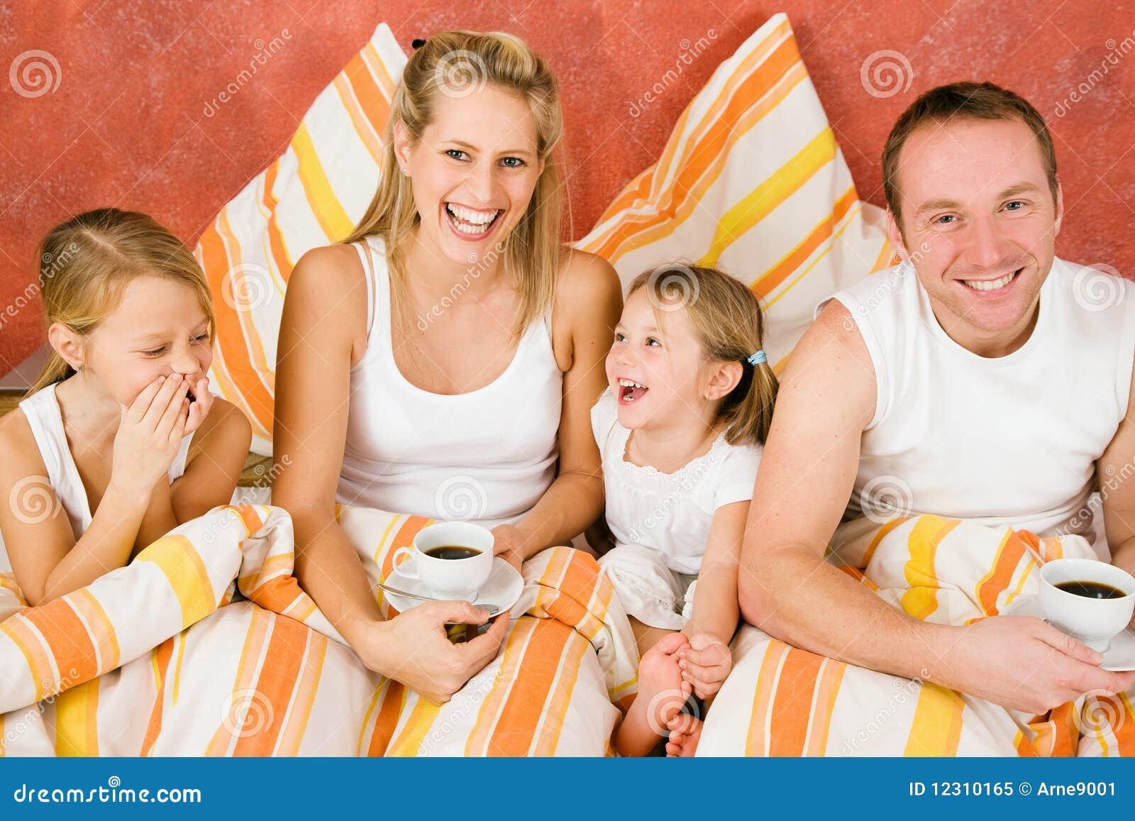 Family of four in bed having breakfast
