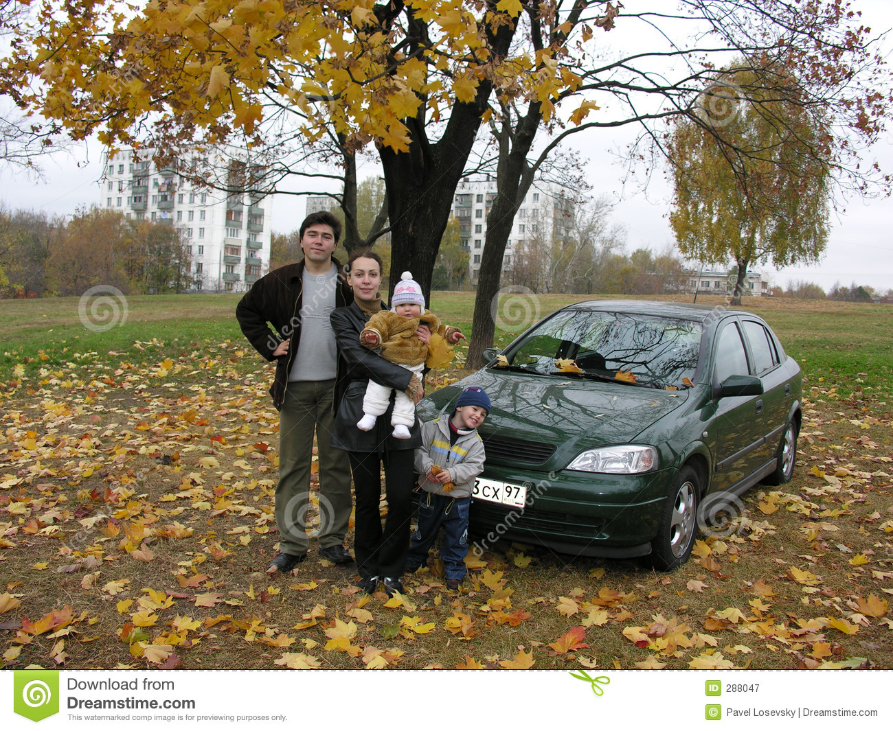 Family of four and car and autumn