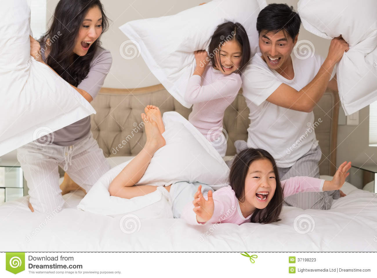 Family Of Four Having Pillow Fight On Bed Stock Image ...