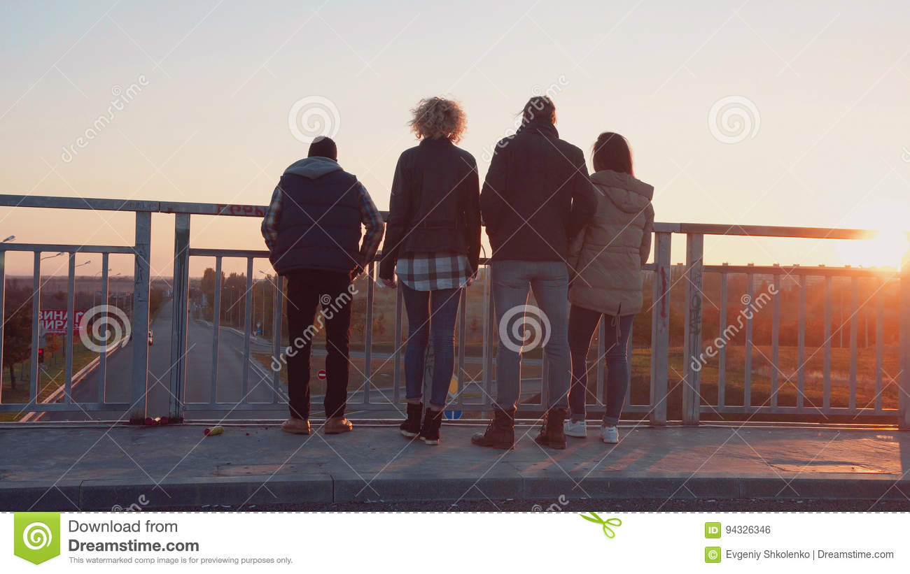 Family of four stands at barrier to observe nature