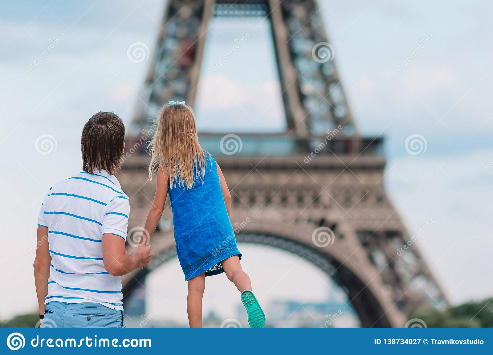 Little Cute Girl And Her Father In Paris Near Eiffel Tower During
