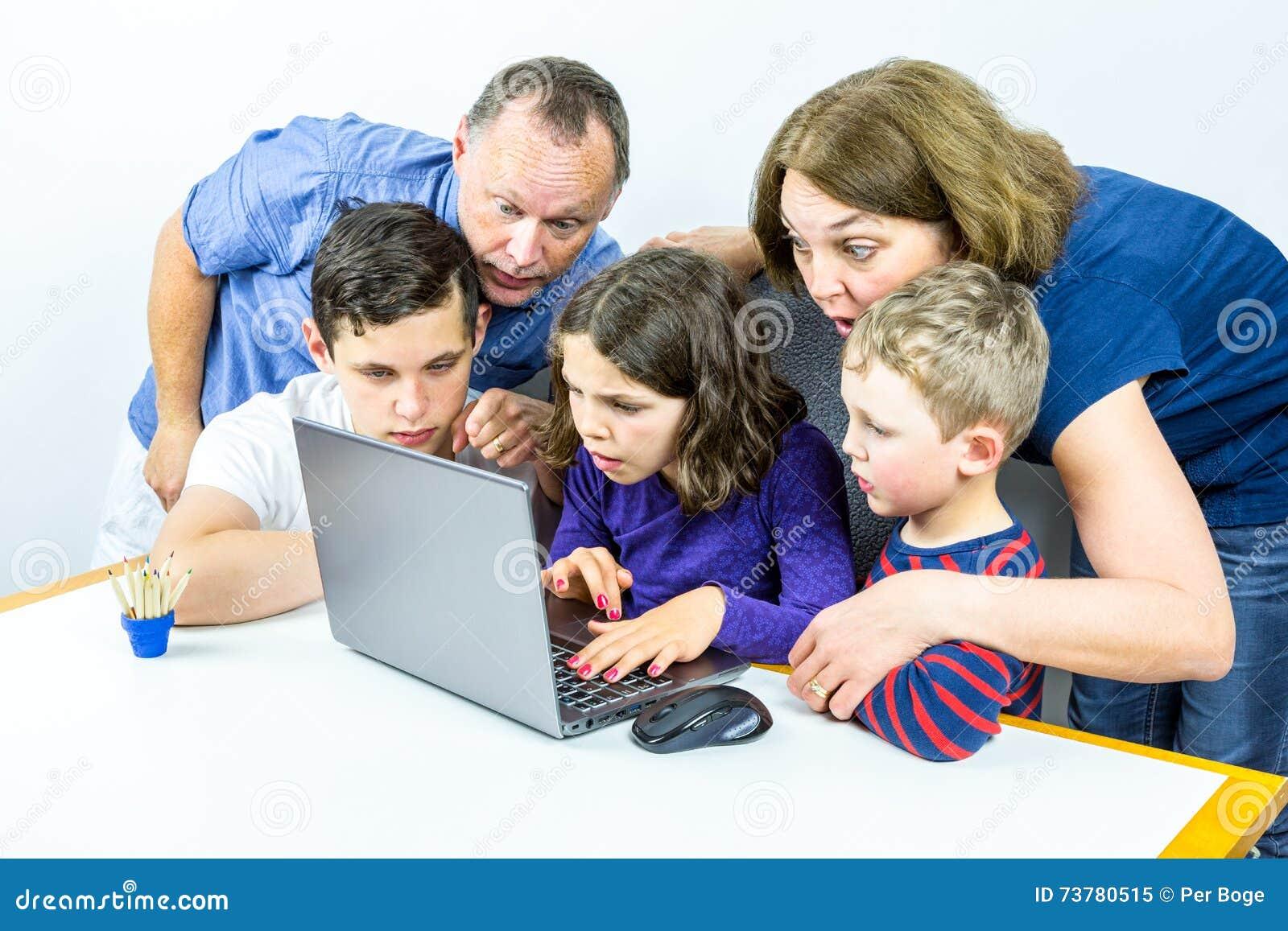 Family gathered around laptop looks at shocking content on internet, studio shot.