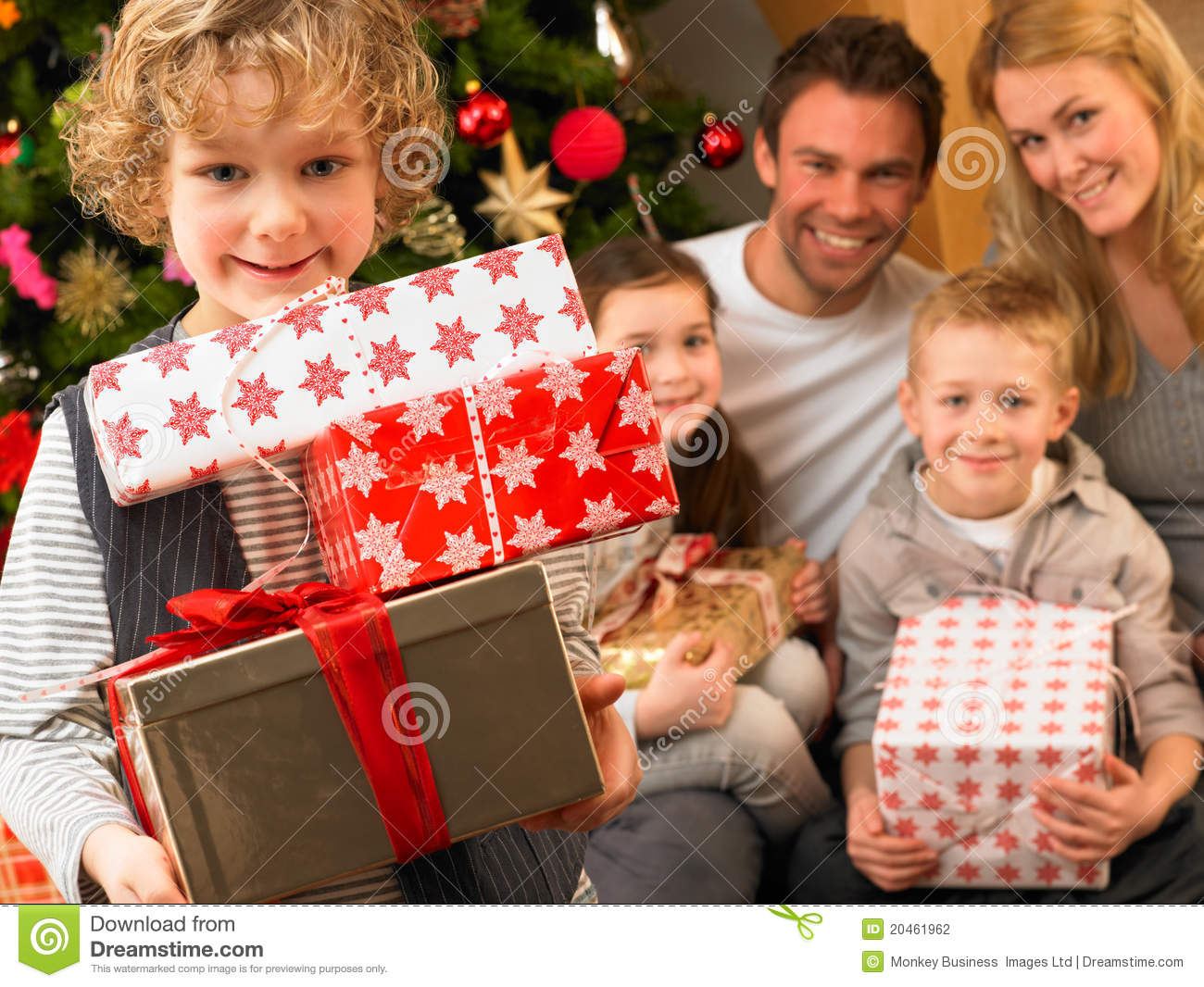 Family With Gifts In Front Of Christmas Tree Stock Photo