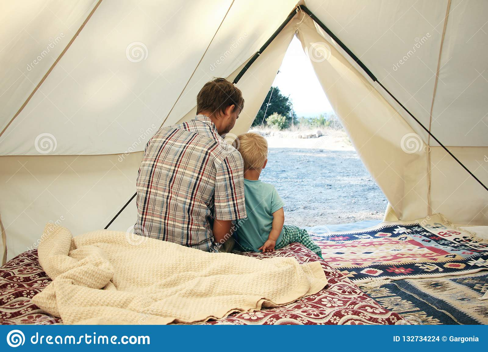 Father and his toddler son inside big c&ing tent with cozy interior. Luxury travel accomodation into the forest. & Family Glamping. Father And His Toddler Son Inside Big Camping Tent ...