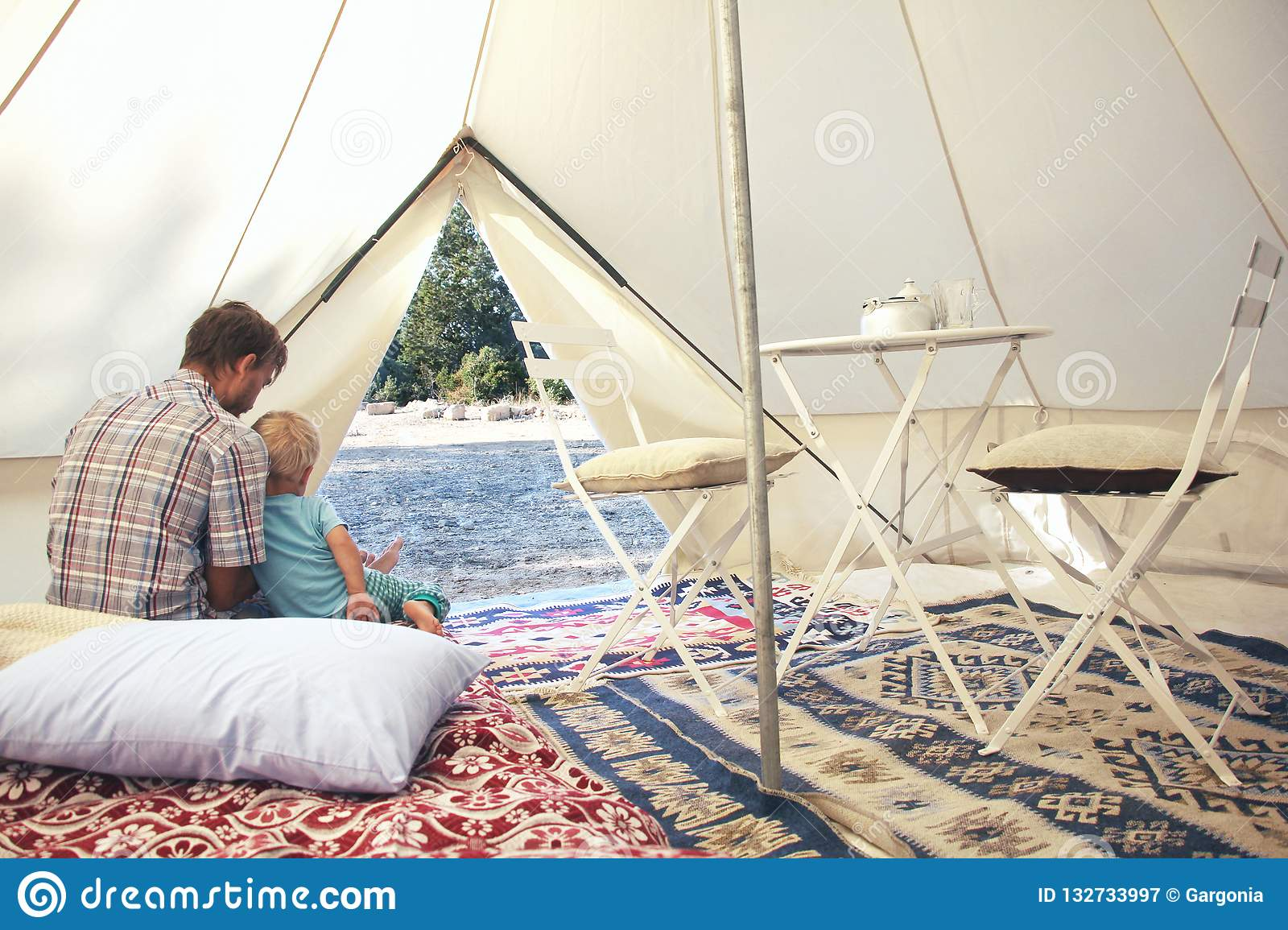 Father and his toddler son inside big c&ing tent with cozy interior. Luxury travel accomodation into the forest & Family Glamping Outdoor Vacation. Father And His Toddler Son Inside ...