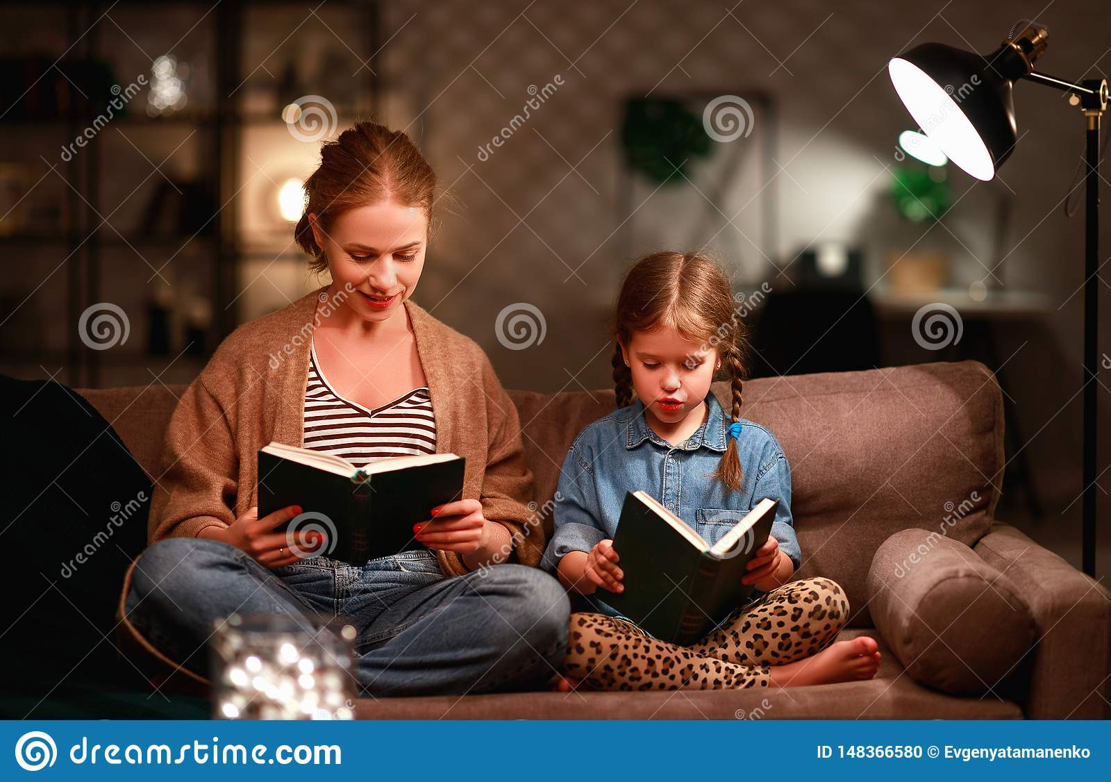 Family before going to bed mother reads to her child daughter book near a lamp in evening