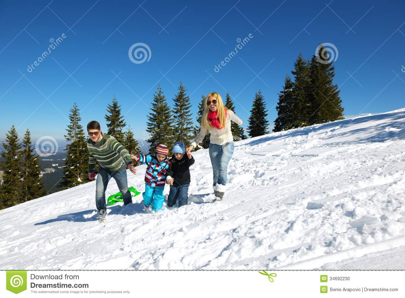 Family having fun on fresh snow at winter stock photo for Vacation in the snow